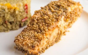 zoomed image of a salmon fillet with sesame seeds, with quinoa side on the background