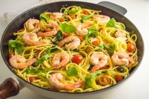 close-up of a skillet with shrimp, tomatoes and spinach pasta topped with arugula