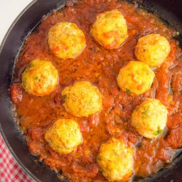 A cast iron skillet on a table filled with nine turkey meatballs cooked in tomato sauce