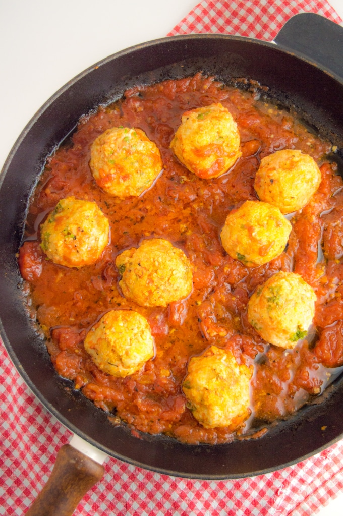 A cast iron skilled on a table filled with nine turkey meatballs cooked in tomato sauce
