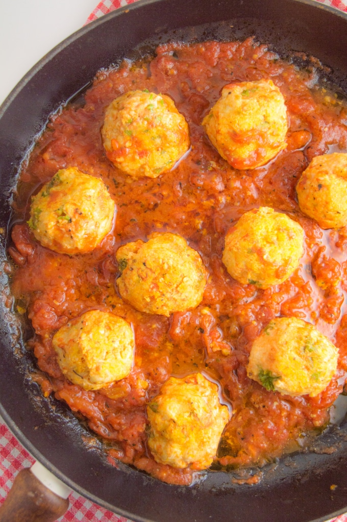 A cast iron skilled filled with nine turkey meatballs cooked in tomato sauce