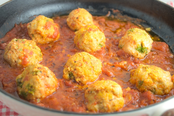 turkey meatballs cooking in tomato sauce, inside an iron casted skillet