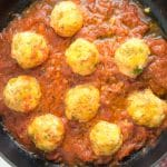 close-up of turkey meatballs cooking in tomato sauce, inside an iron casted skillet