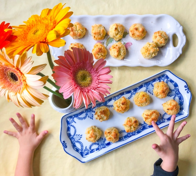 Two platters with coconut macaroons, kid's hands pointing at them, on a table decorated with flowers