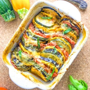 A small oven dish with colorful baked vegetable slices, topped with cheese
