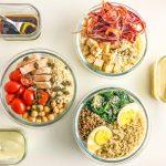 três bowls redontos com saladas e três recipientes rectangulares com molhos