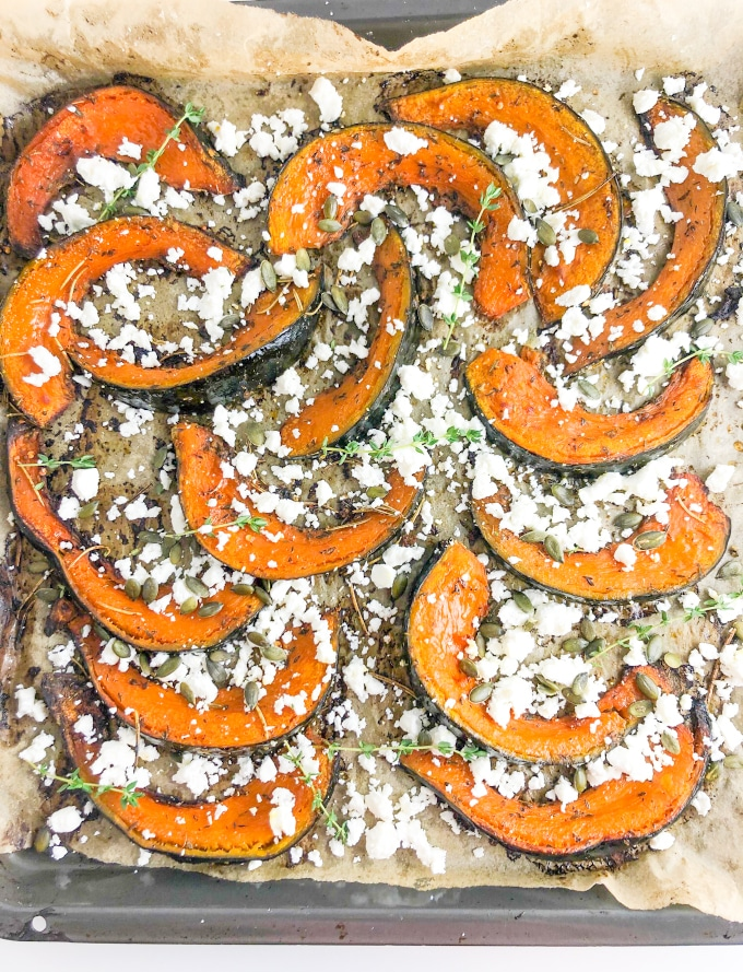 Roast pumpkin wedges with feta on a baking tray