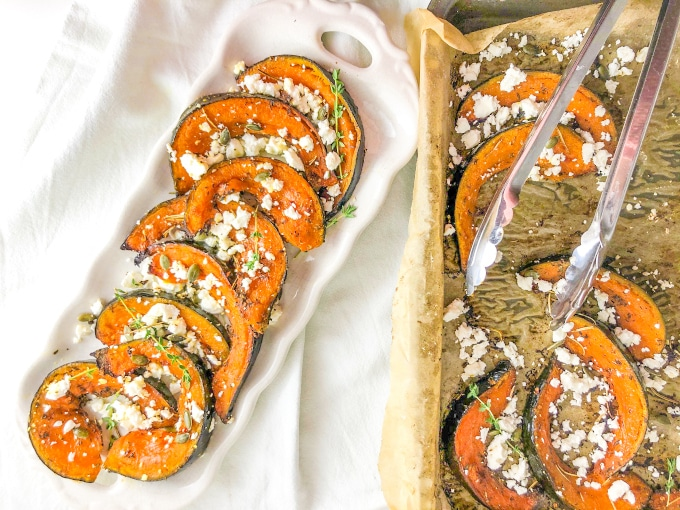 A plate and a tray filled with roast pumpkin wedges topped with feta and thyme