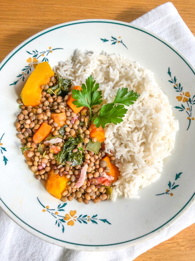 a plate with half lentils with vegetables, half rice