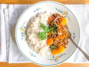 um prato com metade arroz branco, metade lentilhas com legumes