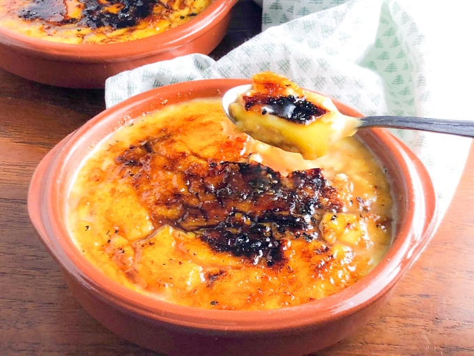 spoonflul of creme brulee in a brown ramekin