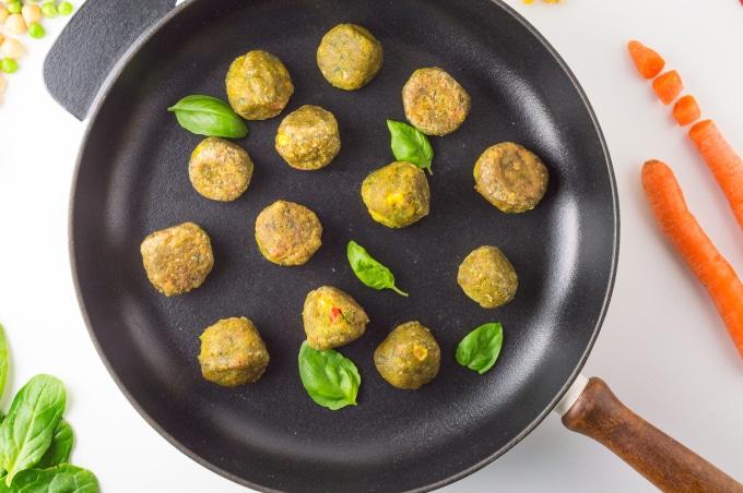 almôndegas vegetarianas numa frigideira de ferro fundido rodeada de legumes