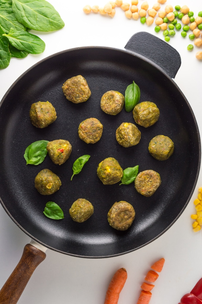 frigideira com almôndegas, rodeada de vegetais e grãos
