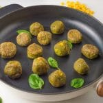 vegetable balls on a cast iron skillet, surrounded by vegetables