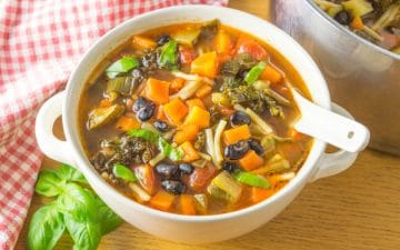 bowl of minestrone soup with a spoon inside