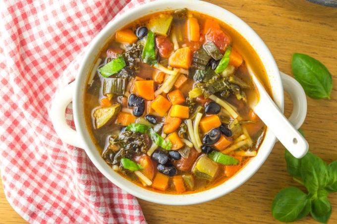 taça com sopa minestrone e folhas de manjericão