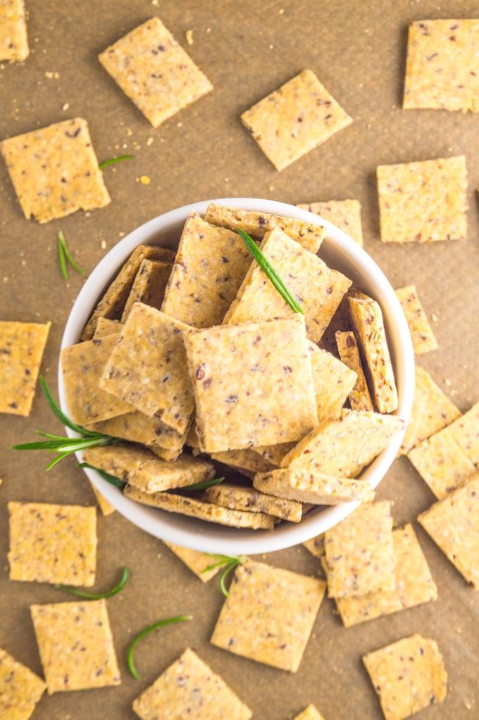 imagem vista de cima de uma taça com crackers e crackers espalhados num tabuleiro