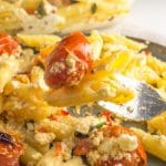 a fork with baked feta pasta and a cherry tomato