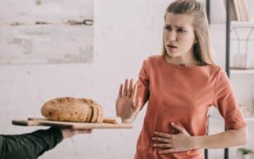Mulher recusa uma bandeja de pão com a mão e com a outra mão na barriga