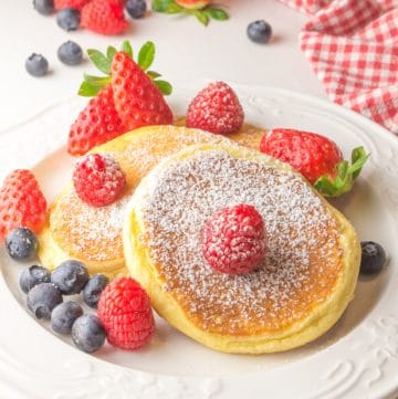 three fluffy pancakes on a plate topped with fruit