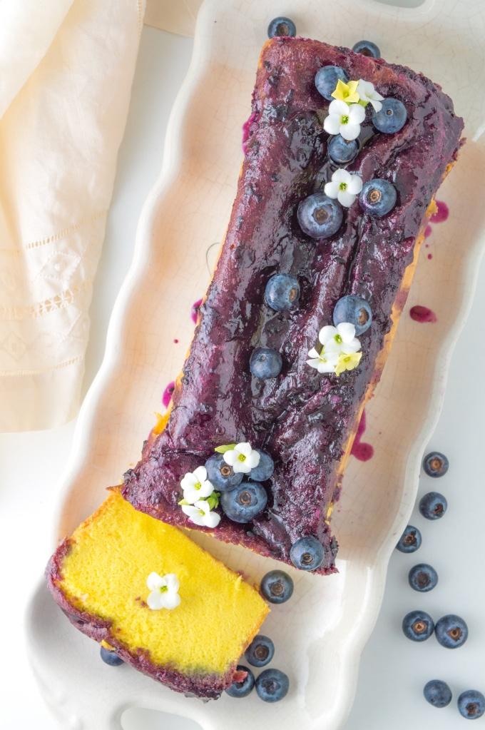 pão de ló fatiado, decorado com mirtilos e flores