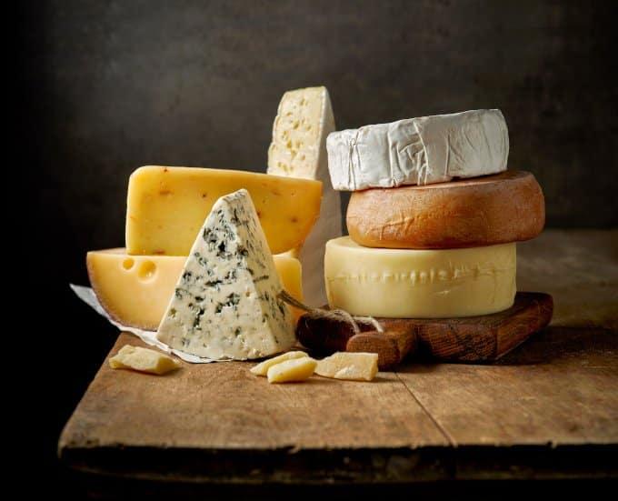 diferentes tipos de queijo empilhados em cima de uma tábua