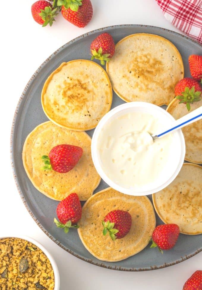 seis panquecas, um iogurte e morangos num prato