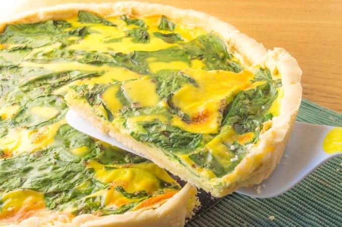 ação de retirar uma fatia de uma tarte de espinafres e queijo