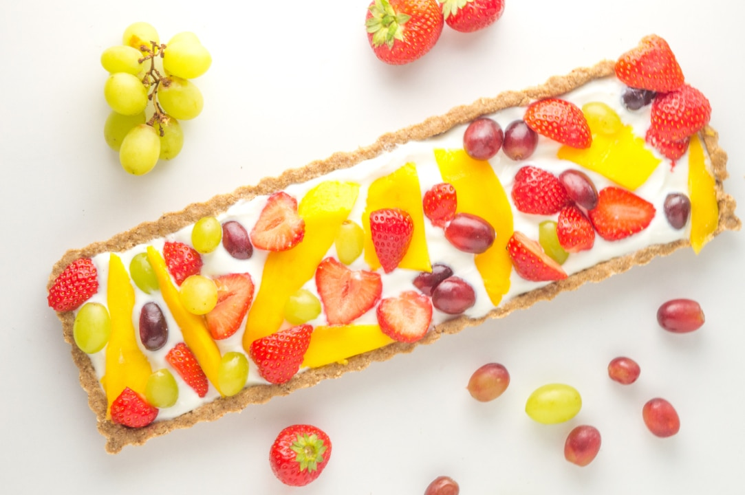 tarte de fruta low fodmap inteira com uvas e morangos à volta