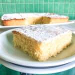 pormenor de uma fatia de bolo de limão low fodmap num prato com bolo ao fundo